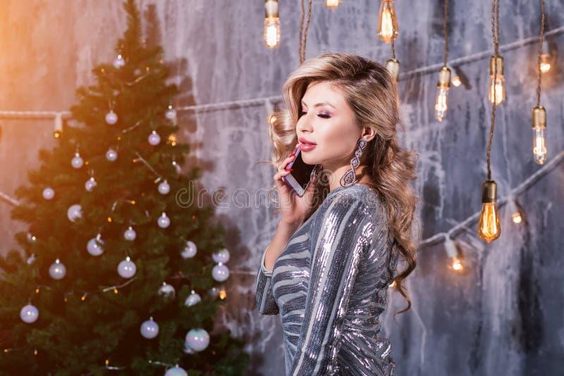 在打电话的圣诞树附近的愉快的少妇 免版税库存照片