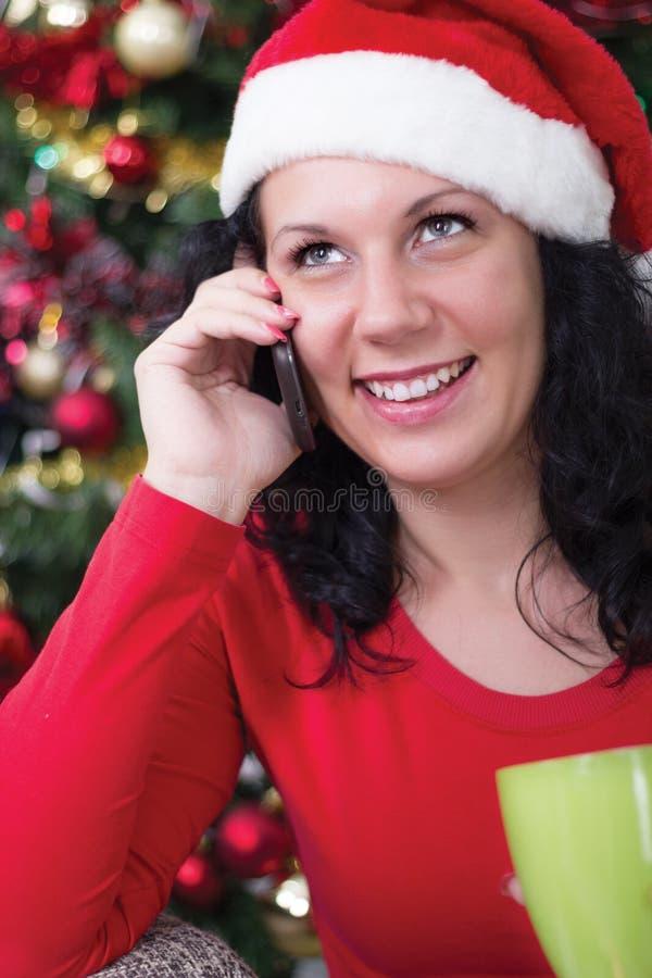 在打电话的圣诞树附近的愉快的少妇 库存照片