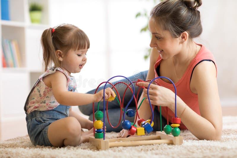 在托儿所在家哄骗与教育玩具的女孩戏剧 看她聪明的女儿的愉快的母亲 免版税库存照片