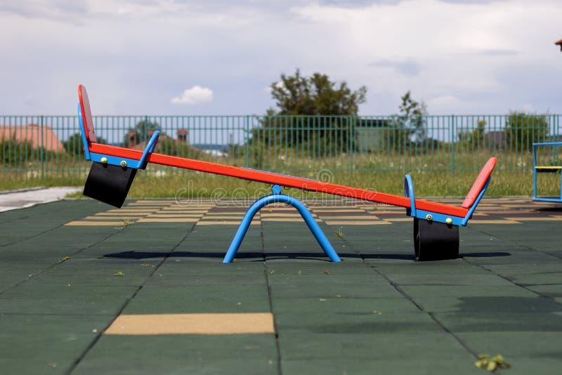 在托儿所操场的新的现代塑料明亮的五颜六色的蓝色和红色空的玩具跷跷板摇摆有在明亮的s的软的橡胶地板的 库存图片