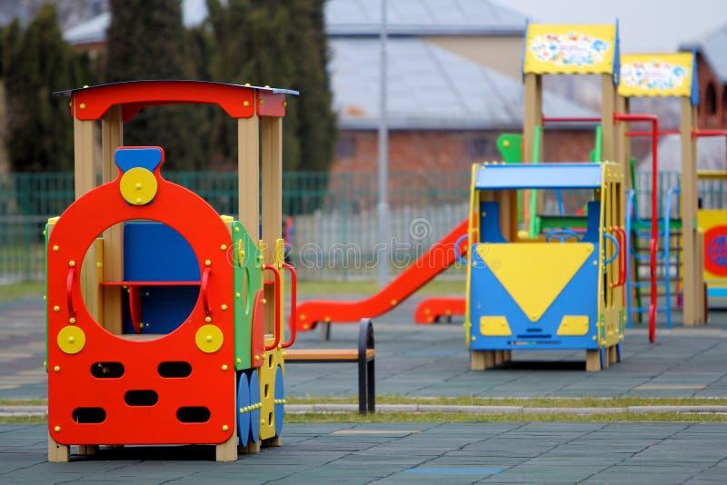 在托儿所操场的明亮的五颜六色的大玩具汽车有软的橡胶地板的在明亮的晴朗的夏日 完善的地方为 免版税库存图片
