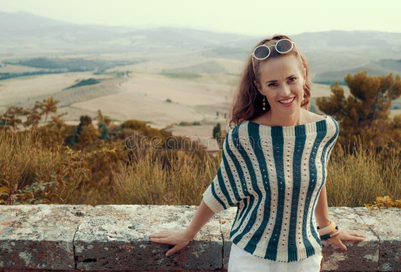 在托斯卡纳的风景的前面微笑的年轻旅游妇女 库存照片