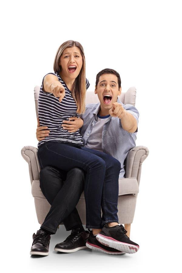 在扶手椅子供以座位的年轻夫妇指向照相机和la 库存照片