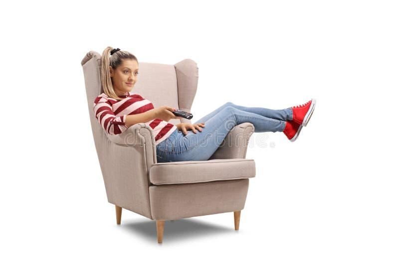 在扶手椅子安装的少妇看电视 免版税图库摄影