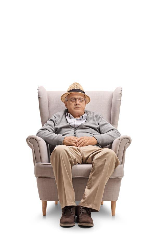 在扶手椅子安装的成熟人 免版税库存图片