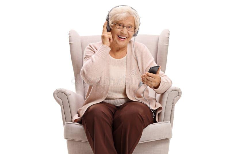 在扶手椅子安装的资深妇女听到在电话的音乐 免版税库存照片