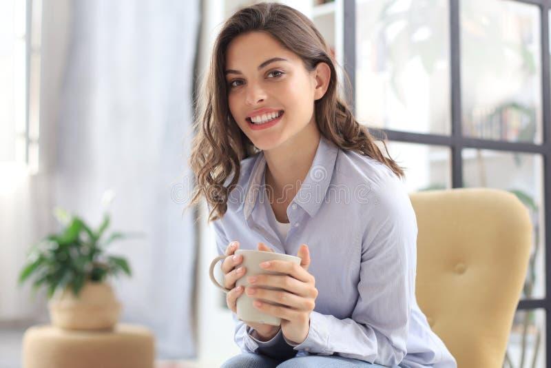 在扶手椅子的微笑的年轻女性开会在客厅,拿着一杯咖啡和看照相机 库存图片