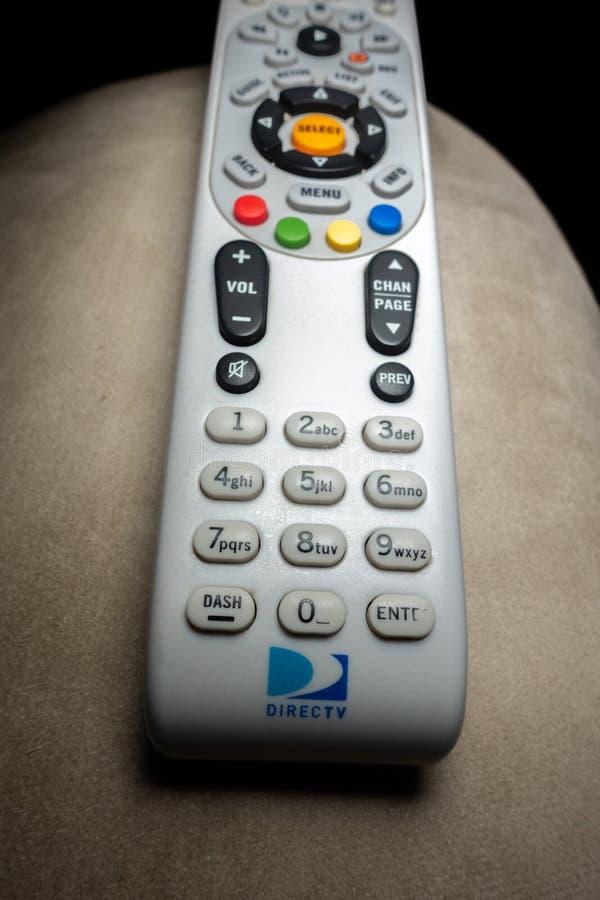 在扶手椅子的DirecTV遥远的被射击的特写镜头有黑背景 库存照片