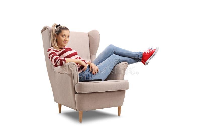 在扶手椅子看着电视安装的年轻女人 库存图片