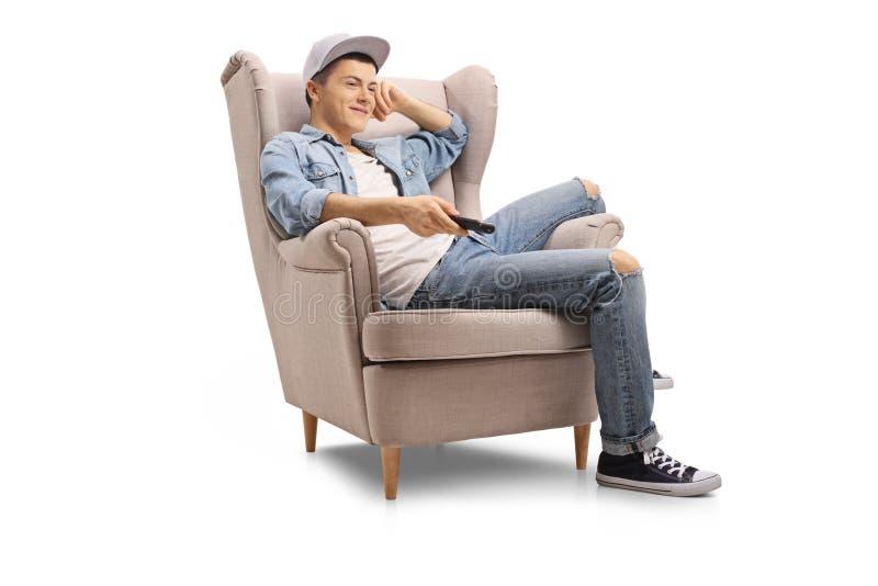 在扶手椅子观看的电视安装的十几岁的男孩 库存照片
