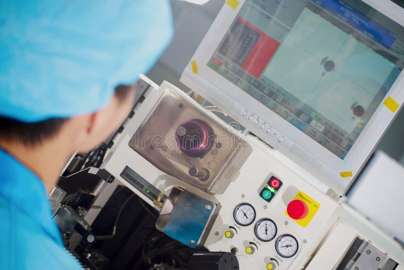 在技术员屏幕上的亚洲工厂劳工神色 免版税库存图片