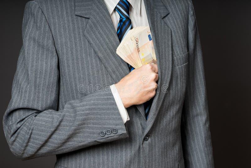 在投入钞票的衣服的商人在他的夹克衣胸袋 商人拿着现金,堆五十欧元金钱 Pers 免版税图库摄影