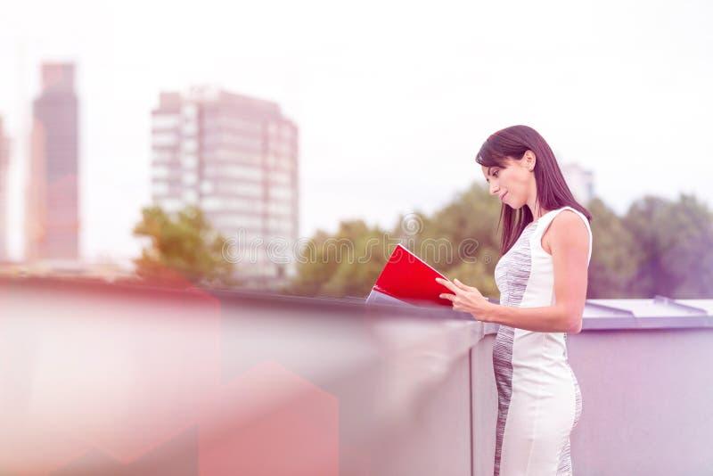 在护墙的确信的女实业家读书文件在办公室大阳台 免版税库存照片