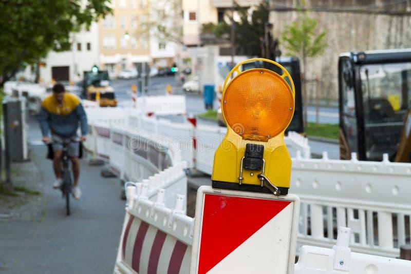 在护拦的橙色建筑街道界灯 路负面因素 免版税库存照片