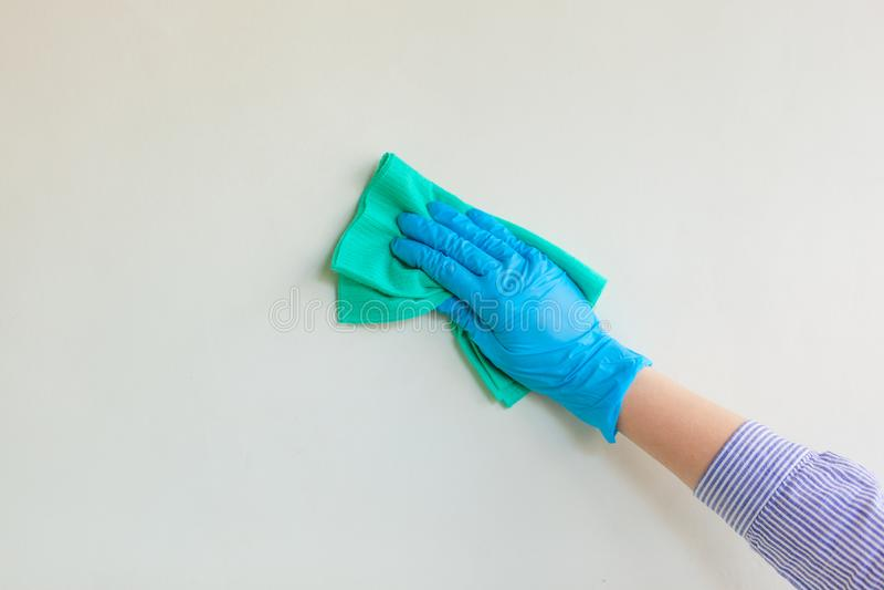 在抹从尘土的蓝色橡胶防护手套的雇员手墙壁与干燥旧布 商业清洗的公司 免版税库存图片