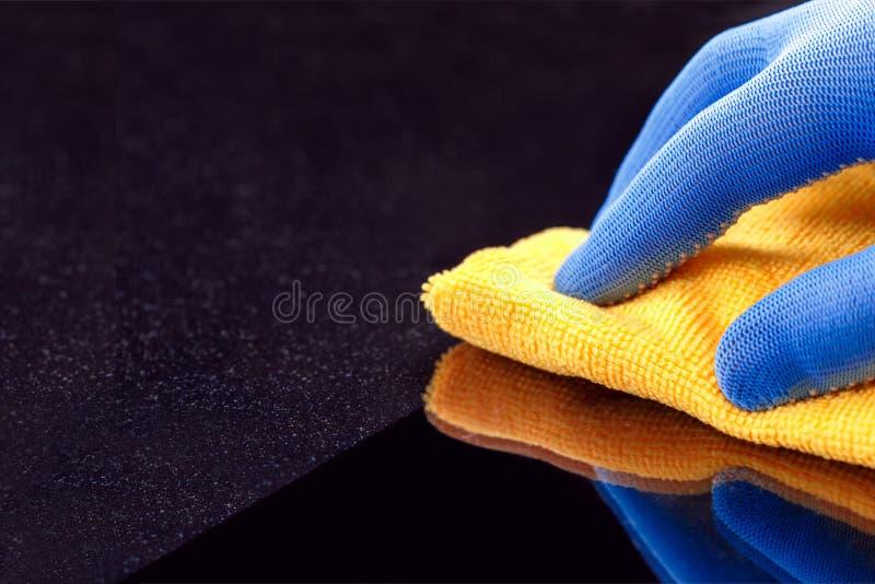 在抹在家具的防护手套的手尘土层数与黄色干燥旧布 r 免版税库存图片