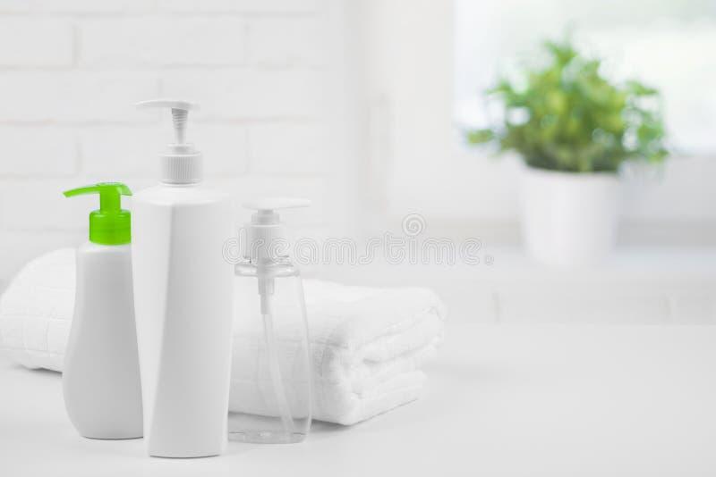 在抽象卫生间窗口背景的白色毛巾和化妆用品分配器 免版税库存照片