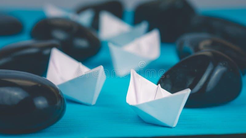 在抽象岩石石头之间的领导白皮书小船主角进一步船在蓝色背景 免版税图库摄影
