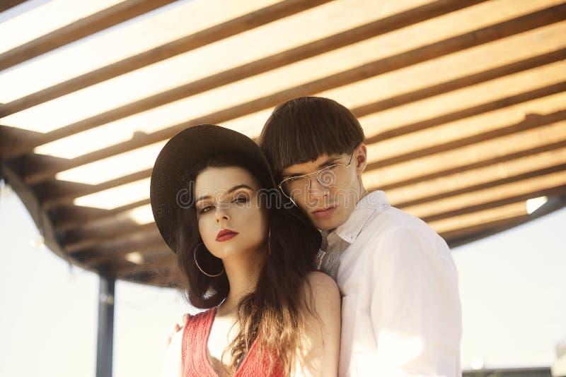 在抽象背景的美好的时兴的夫妇 时兴的行家 一个红色礼服和黑大帽子的女孩 免版税库存照片