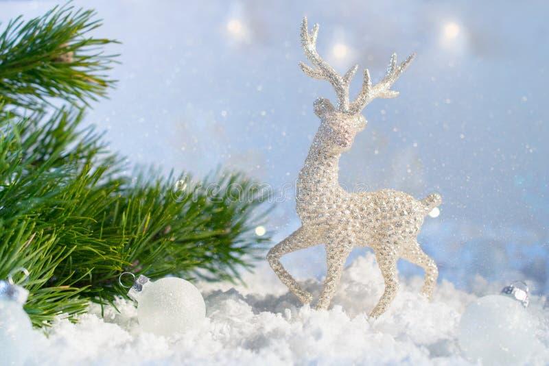 在抽象闪烁光背景,软的焦点的圣诞装饰 在雪的银色鹿反对模糊的l背景  免版税库存照片
