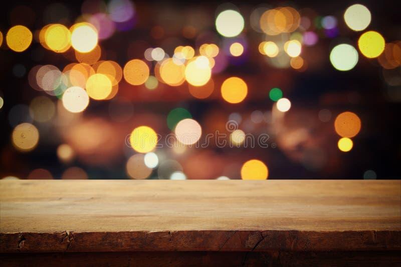 在抽象餐馆前面的木桌点燃背景 免版税图库摄影