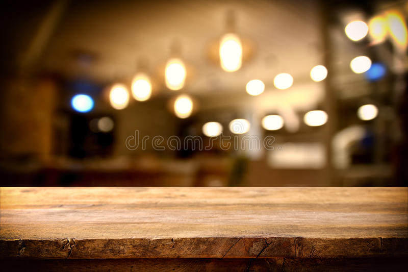 在抽象餐馆前面的木桌点燃背景 库存照片