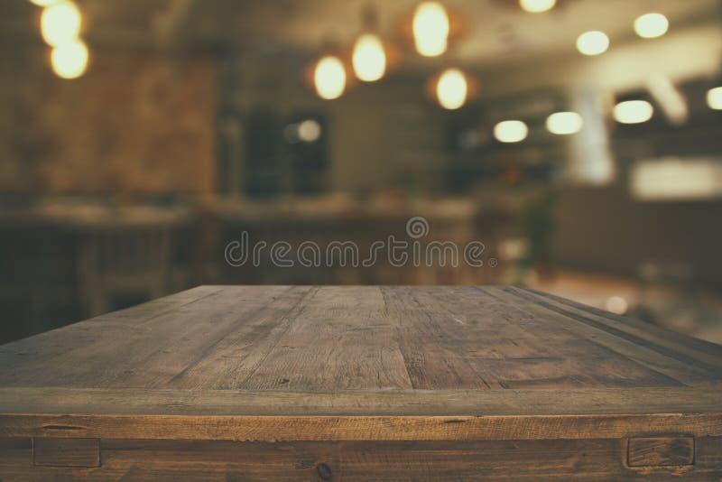 在抽象餐馆前面的木桌点燃背景 免版税库存图片