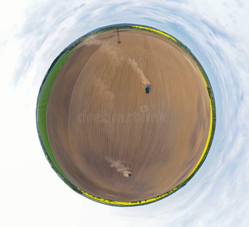 在拉扯犁的蓝色拖拉机的空中360度全景,土壤为种子播种做准备,做土云彩的拖拉机 皇族释放例证