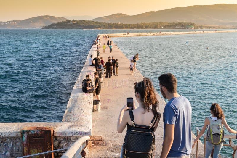 在拍与上午的沃洛斯港的桥梁的一对夫妇照片 免版税库存图片