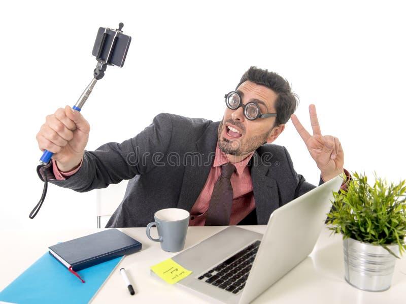 在拍与手机照相机和棍子的办公桌的滑稽的书呆子商人selfie照片 免版税图库摄影