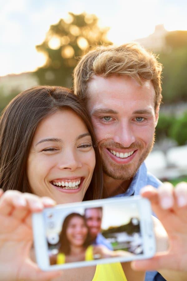 在拍与智能手机的爱的夫妇selfie照片 免版税库存照片