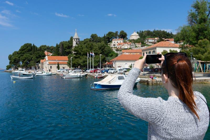在拍亚得里亚海的照片有智能手机的海岸镇的少女身分在Cavtat,克罗地亚 红色顶头马尾 免版税库存图片