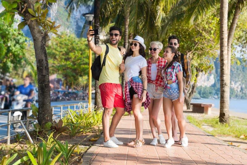 在拍Selfie照片的海滩的青年人小组细胞聪明的电话暑假,愉快的微笑的朋友海假日 免版税图库摄影