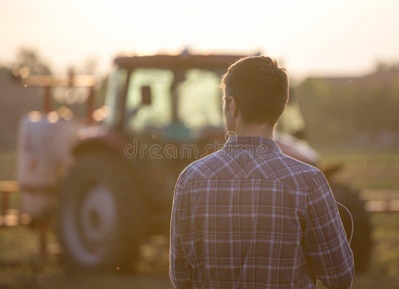 在拖拉机前面的农夫在领域 库存图片