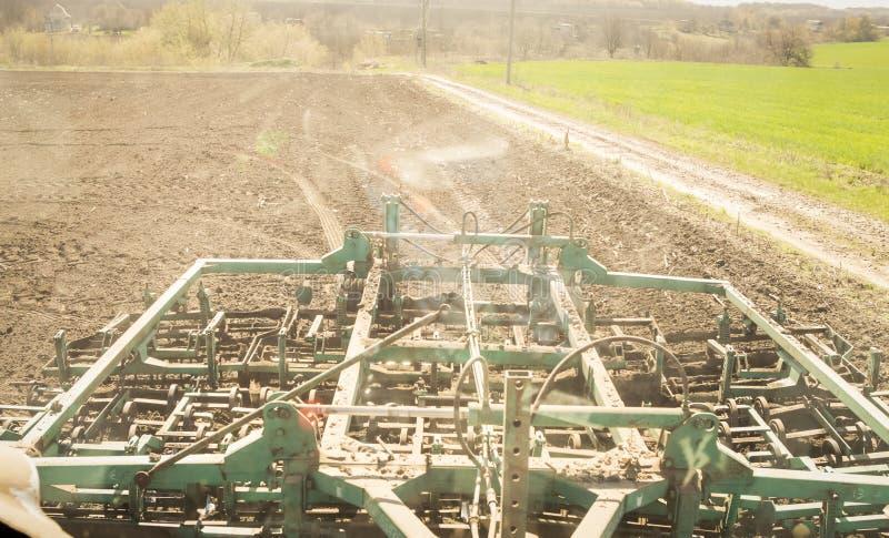 在拖拉机后的耕地机在绿色领域附近的被耕的土壤 免版税库存图片
