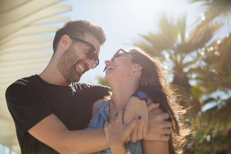 在拥抱一起笑的爱的愉快的夫妇 免版税图库摄影