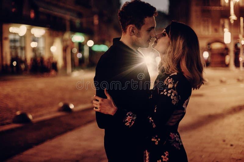 在拥抱和亲吻在晚上城市的爱的时髦的吉普赛夫妇 库存照片