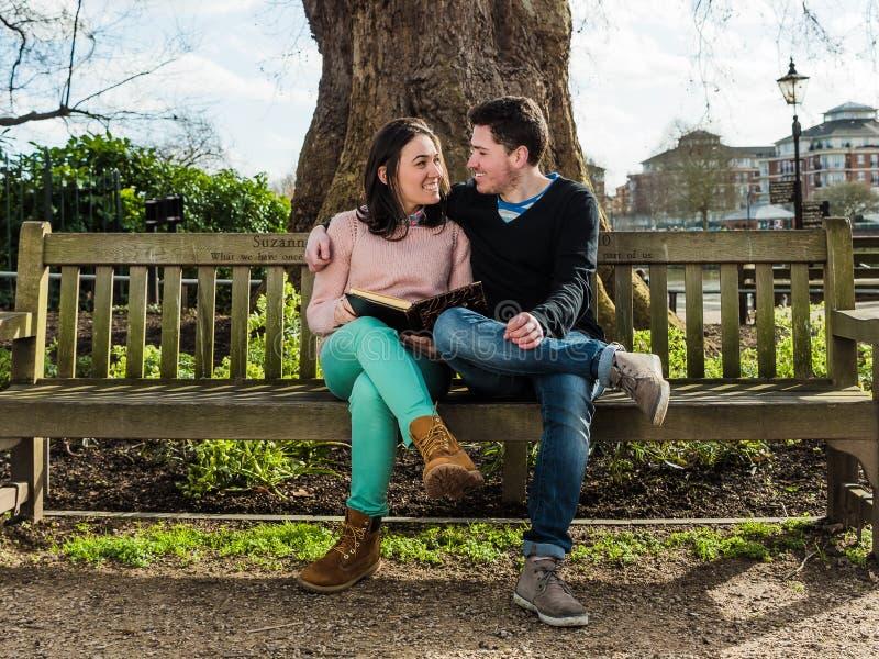 在拥抱和约会坐一条长凳的爱的夫妇在公园 免版税库存照片