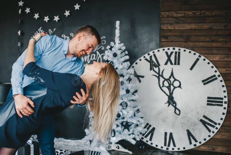 在拥抱和跳舞午夜探戈的爱的美好,年轻夫妇以壁钟为背景 免版税库存照片