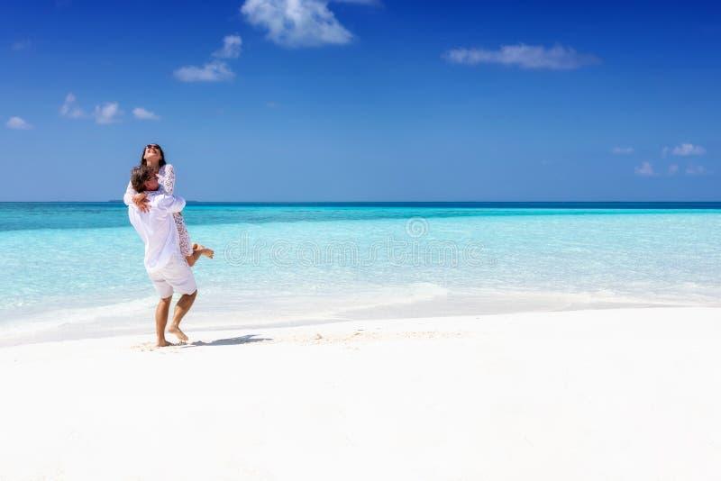 在拥抱在一个热带海滩的白色夏天衣物的夫妇 库存照片