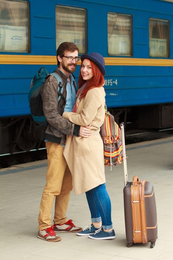 在拥抱在火车站的街道的一对愉快的夫妇的旅行的以后遭遇 美好的晚上温暖的阳光 免版税库存图片