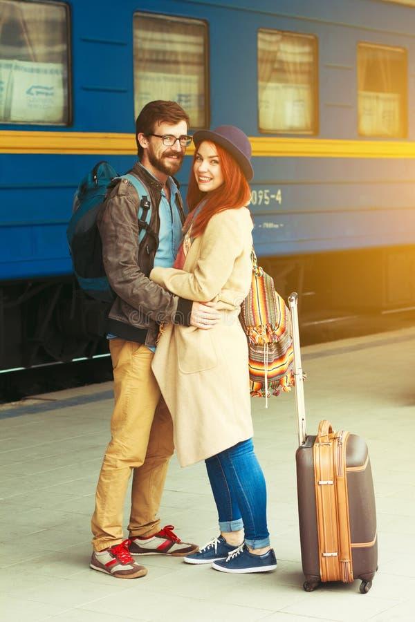 在拥抱在火车站的街道的一对愉快的夫妇的旅行的以后遭遇 美好的晚上温暖的阳光 库存图片