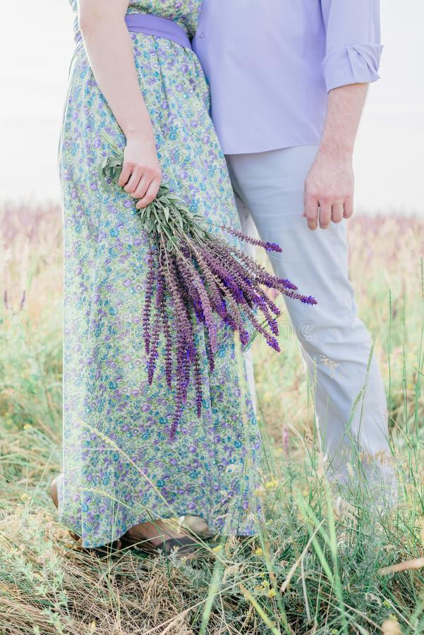 在拥抱在花的领域的爱的逗人喜爱的夫妇,播种 库存照片
