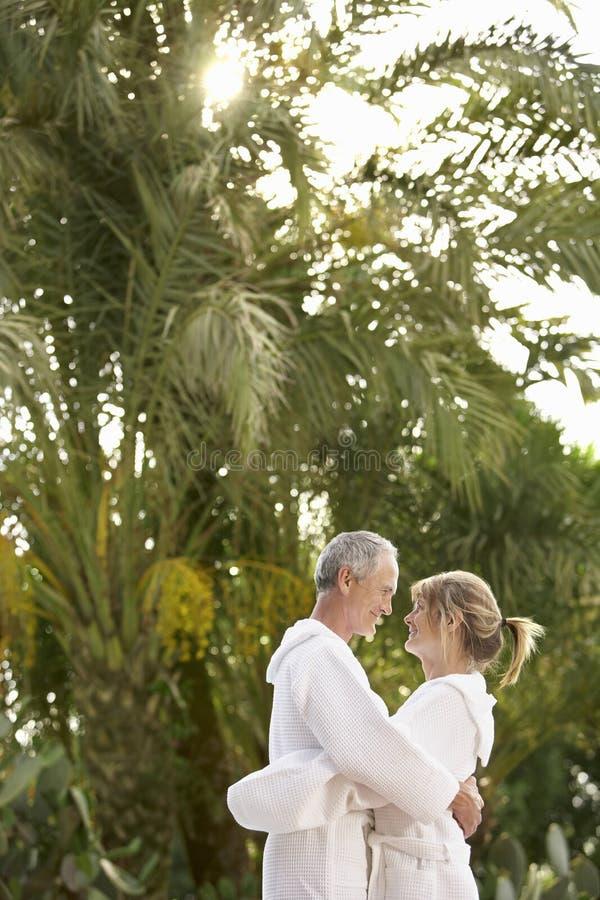 在拥抱由棕榈树的浴巾的夫妇 免版税库存图片