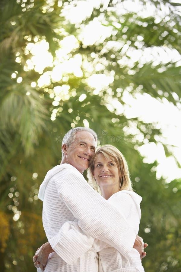 在拥抱由棕榈树的浴巾的夫妇 库存照片