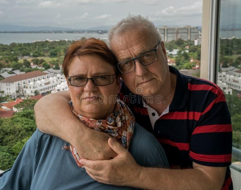 在拥抱的一对年长夫妇在他们的房子阳台站立  家庭田园诗,爱在一岁月以后 免版税库存图片