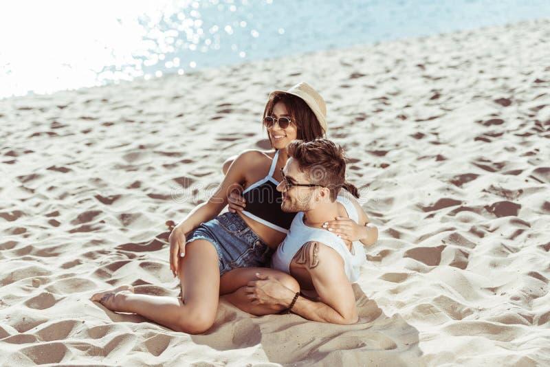 在拥抱的太阳镜的年轻夫妇,当坐在沙滩时 库存照片