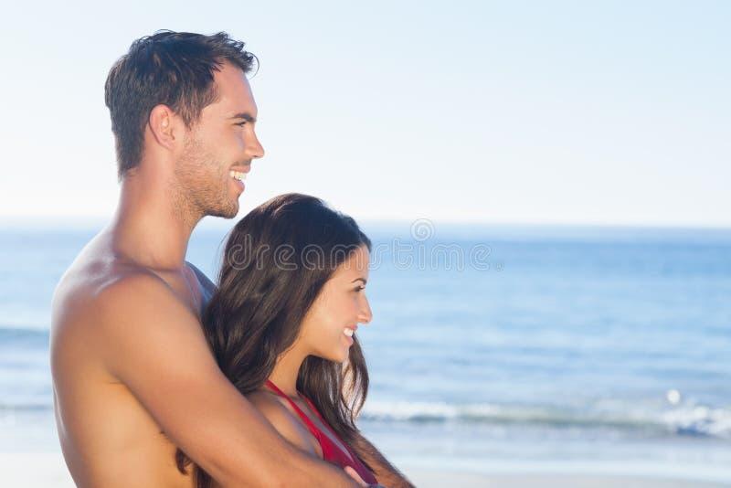 在拥抱的泳装的愉快的夫妇,当看水时 免版税库存照片