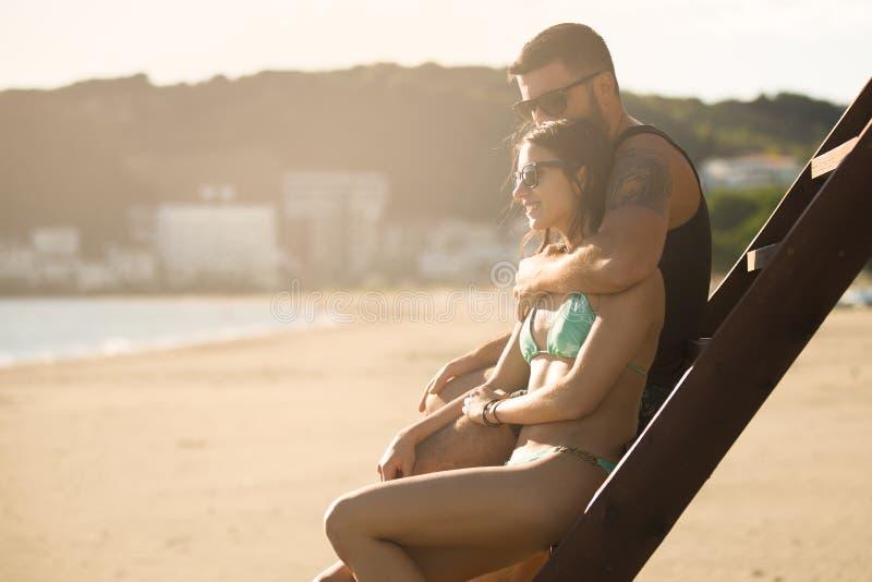 在拥抱观看的日出日落的浪漫夫妇一起 爱人妇女年轻人 库存图片