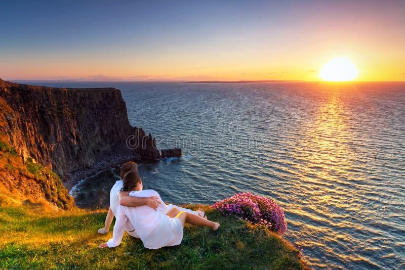 在拥抱观看的日落的夫妇 免版税库存照片